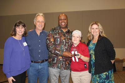 Centennial Middle School football coach Geoffrey Redmond, center, holds the award he received from TASH, an organization advocating for inclusion of disabled adults and children. Flanking him are, from left, Andrea O'Brien of TASH, George Chase, Andrea Tacker and Carol Ann Marusiak. Marusiak and her husband, Chase, are caring for the disabled foster girl whom Redmond made team manager.