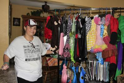 Ahwatukee resident Sabrina Ramirez stacks donated costumes for needy children in her living room pending their distribution. She has been handling costume drives for a dozen years.