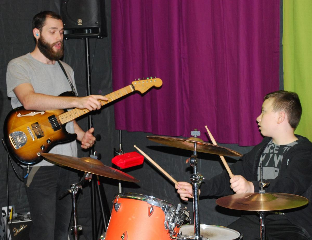 School of Rock instructor Jacob Unterreiner gives some tips for fledgling drummer Aston Rollins during a lesson at the Ahwatukee school. For the most part, teachers there are working musicians.