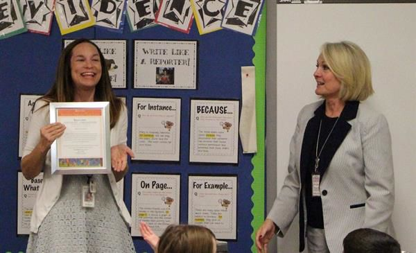 Centennial Middle School teacher Shawndra Reid, left, holds up her certificate as Vesely explains why she was honored. Vesely visited all 25 Kyrene schools last week to bestow honors on select teachers and students.