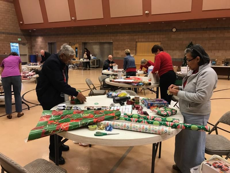 Joe and Elnora Utrera help wrap gifts from the Ahwatukee Kiwanis Club for teens in group foster homes. In the background, from left, Carrie and Howard Chipman, Andi Pettyjohn, Carmen Paiz and Dale Matheson