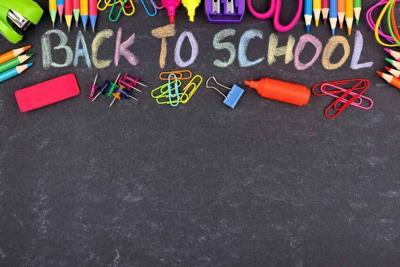 School supplies top border with Back To School written in colorful chalk with against a chalkboard background