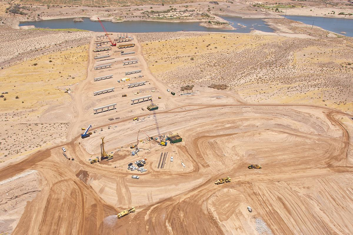 An aerial photo shows progress on the construction of two half-mile-long bridges that will take the South Mountain Freeway over the Salt River just north of Southern Avenue in Laveen.