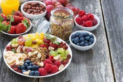 ingredients for a healthy breakfast - berries, fruit, muesli and wooden background, top view