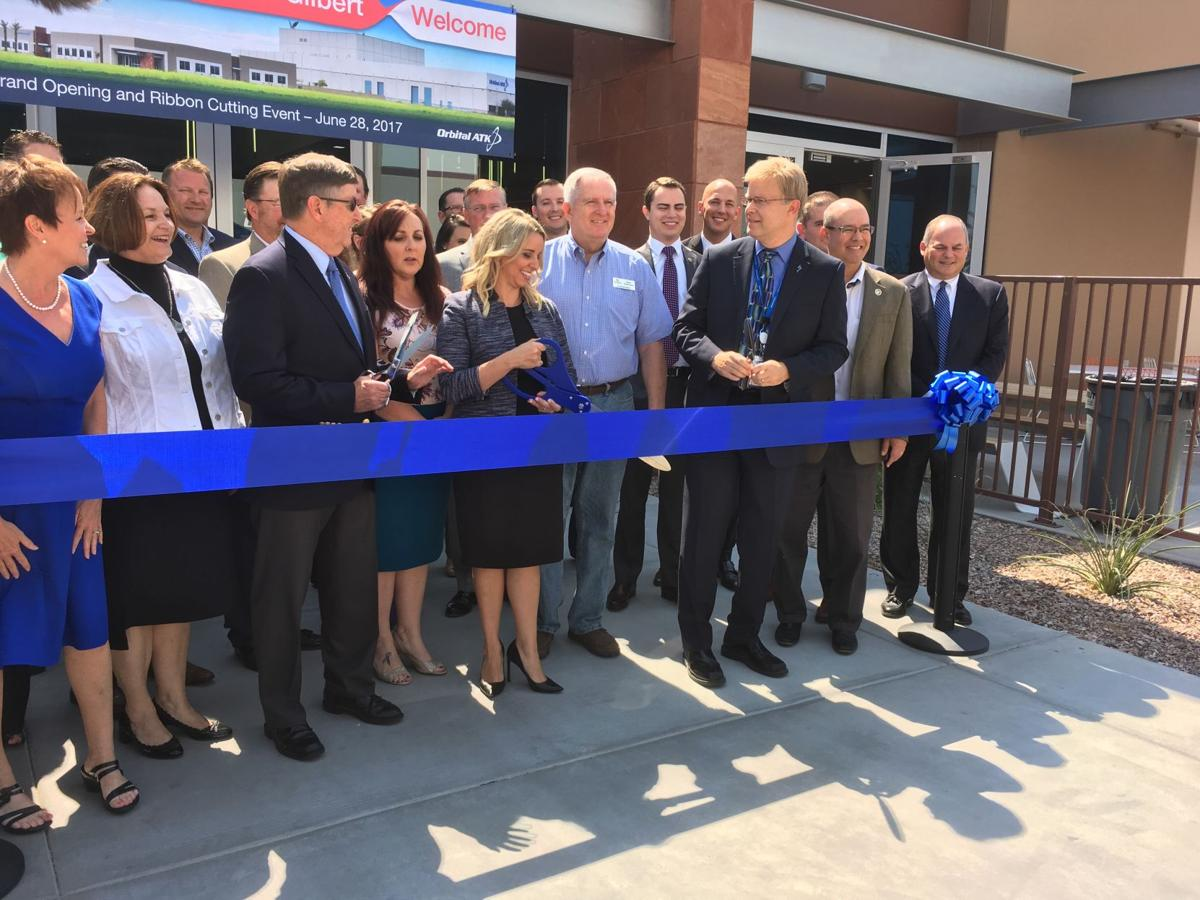 Gilbert Mayor Jenn Daniels (center) is flanked by fellow ribbon-cutters Gilbert Site Manager Rick Kettner (right) and Space Systems Group President Frank Culbertson, along with other city and company officials, at the opening of Orbital ATK's new facility.