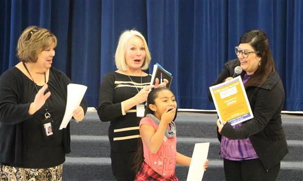 Jalyssa Engel, a student at Colina Elementary, is stunned to get a certificate for her academic accomplishments. Looking on are, from left, Principal Kelley Brunner, Superintendent Jan Vesely and an Urban Air Adventure Park representative.
