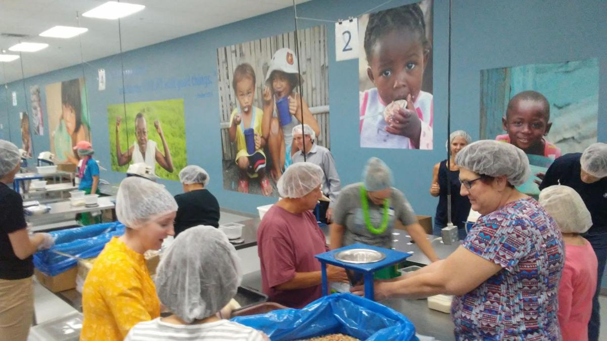 Times Publications employees fill bags of food at Feed My Starving Children's packing center in Mesa.