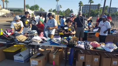 """Volunteers for ASU Project Humanities' biweekly Saturday effort to help homeless people in downtown Phoenix sorted clothing and toiletries for people to """"shop"""" on June 3."""