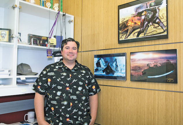 "Chandler City Councilmember René Lopez stands by ""Star Wars"" paintings in his office. He came up with the idea of the Chandler Symphony Orchestra performing a ""Star Wars""-themed concert."