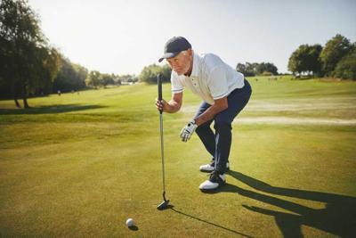 Senior golfer planning his putt on a golf green