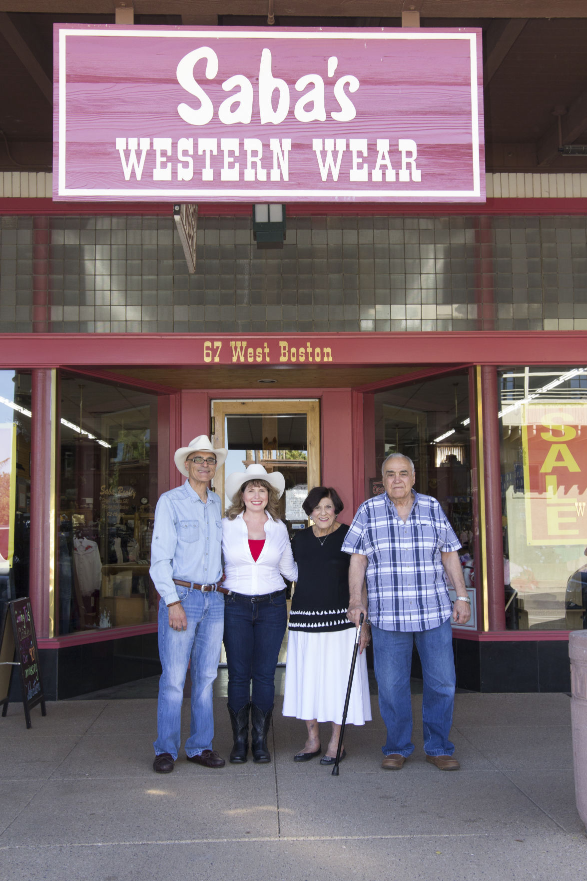 (From left): Davey Saba, his wife Lori Saba, Joan Saba and her husband David Saba Jr. stand in front of the Saba's Western Wear store in downtown Chandler. Joan and David Jr. are the parents of Davey. Saba's is marking its 90th anniversary of the Chandler store.
