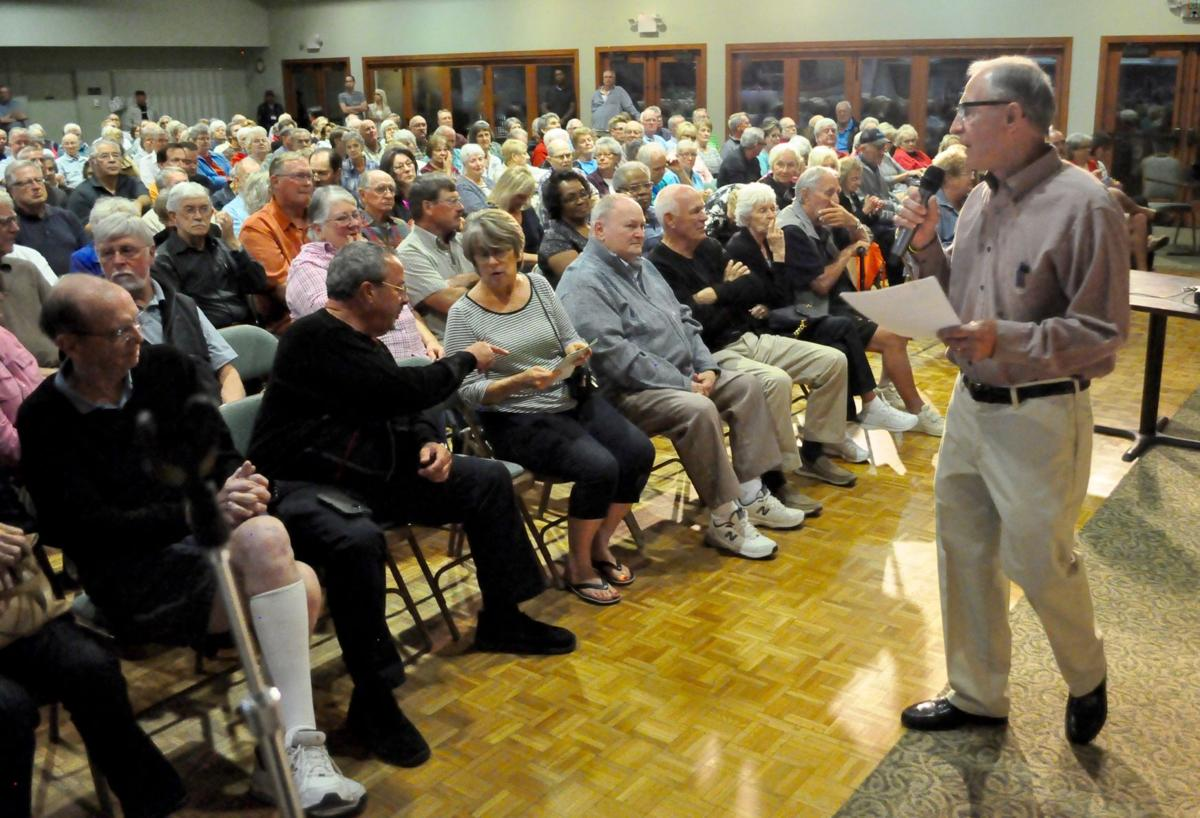 Host Ben Holt speaks to the crowd at the beginning of a Golf Course Town Hall meeting