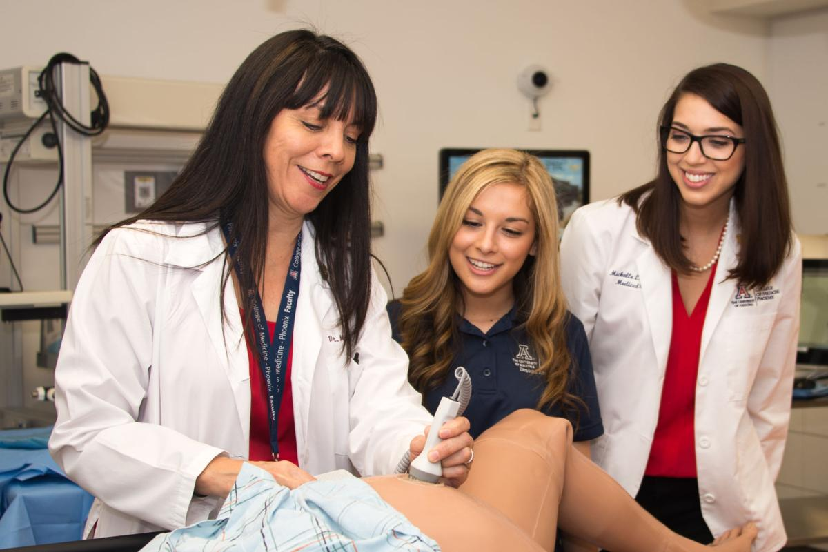 Dr, Maria Manriquez of Ahwatukee demonstrates how to take an ultrasound reading for fourth-year medi school students Stephanie Amaya and Michelle Lynn MMcQuilkin.