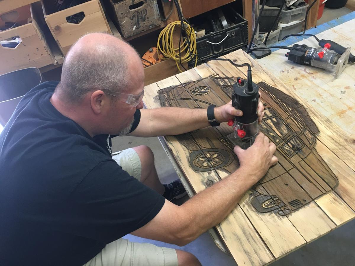 Ahwatukee resident Eric Kruse uses a router to carve out a Volkswagen bus.