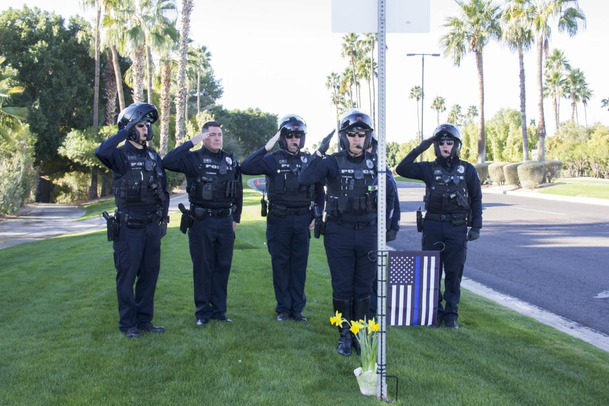 Gilbert Police officers salute a memorial to Lt. Eric Shuhandler at the spot on Baseline Road and Val Vista Drive where he was slain in 2010. The department holds an annual ceremony on the day he died.