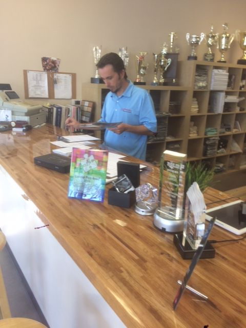 Mike Wapniarski, the graphic design specialist at Ahwatukee Trophies & Corporate Awards examines some artwork in the business' new location in the strip mall on the northwest corner of 48th Street and Warner Road.