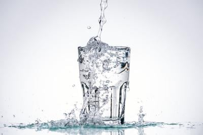 water pouring in full glass on white background with backlit and splashes