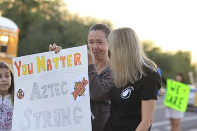 Concerned adults and students stood outside Corona del Sol High School early Nov. 9 with signs supporting students. The gathering came two days after a third student suicide.