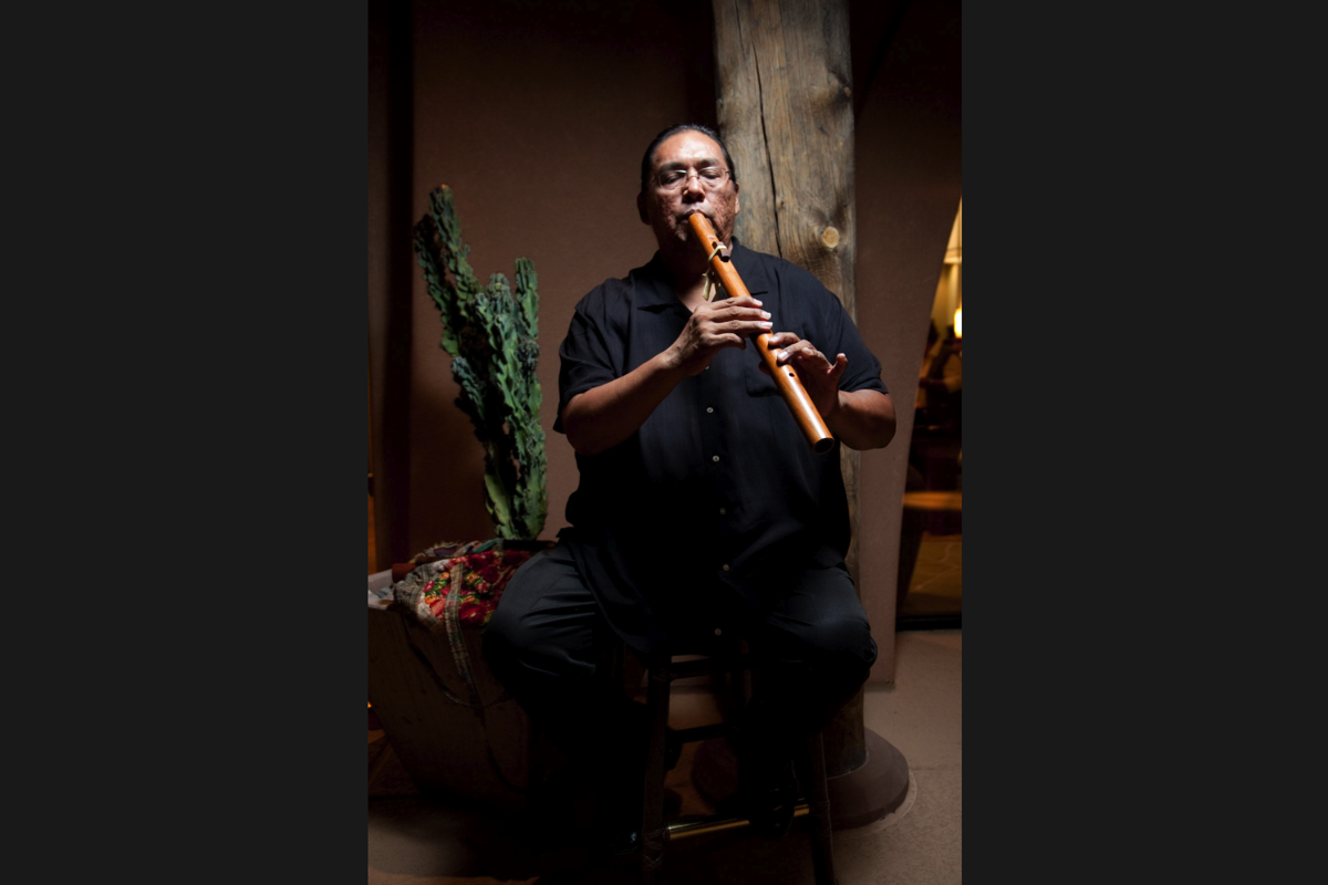 """Aaron White plays a flute to accompany Native American tales during the """"Storytelling & Song"""" series at Wild Horse Pass."""