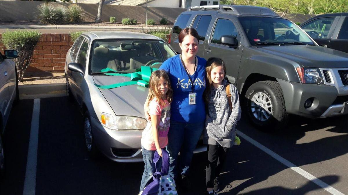 Elisha Smarik hugged two of her three daughters – Bella, left, and Alison – after parents got together and gave her a new used car last Friday, putting a big green bow on the hood.