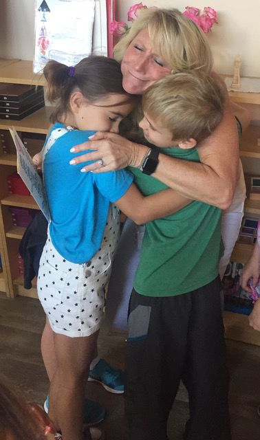 Red Cross representative Cassidy Penney hugs Keystone Montessori students Gia DeAgostine and Zach Treglia after they and classmates presented the agency with nearly $1,800 they collected to help Texans suffering in the aftermath of Hurricane Harvey.