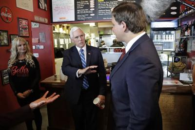 Vice President Mike Pence, center, gestures as he speaks to Florida Gov. Ron DeSantis, right, after ordering lunch at Beth's Burger Bar, Wednesday, May 20, 2020, in Orlando, Fla.