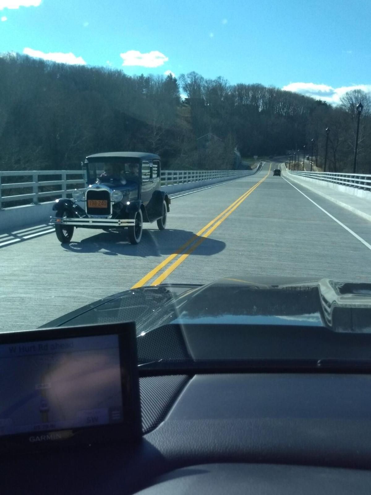 Old timey car on bridge