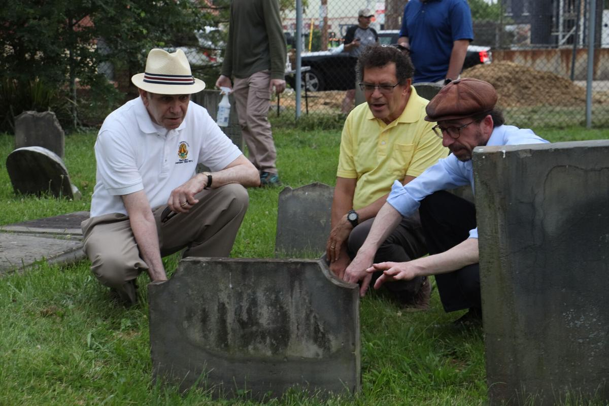 Examining a headstone are, from left to right, Larry Neuman, Board President of Jewish Cemeteries of Greater Cincinnati; Ray Warren, Board Vice President; and David Harris, Executive Director.