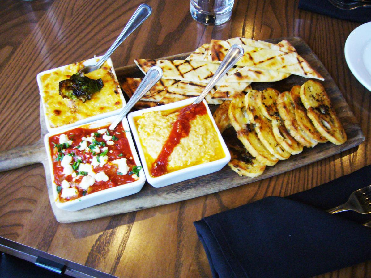 Stone Creek Dining Company serves a triple dip appetizer board, served with grilled French-bread wafer slices and grilled pita strips.