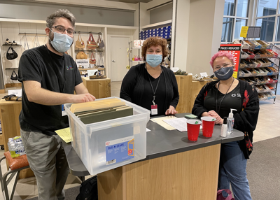 Staff members Jonathan Magrisso, Debbie Zimmerman, and Emma Rankin [L–R], volunteered their time to help coordinate private shopping events that helped community families get new clothing and shoes