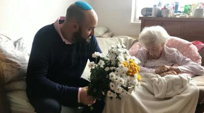 Courtesy of From the Depths via JTA  Krystyna Danko receives flowers from From the Depths founder Jonny Daniels in her Warsaw apartment on her 102nd birthday, July 9, 2019.