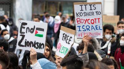 Courtesy of JTA; Photo credit: Austrian Union of Jewish Students. Demonstrators against Israel hold signs at a rally in Vienna, Austria, where protesters chanted in Arabic about a massacre of Jews, May 13, 2021.