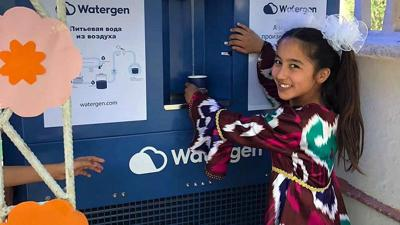 "Courtesy of JNS A girl in Bukhara, Uzbekistan, samples water from an atmospheric water generator known as the ""GEN-350,"" May 2019."
