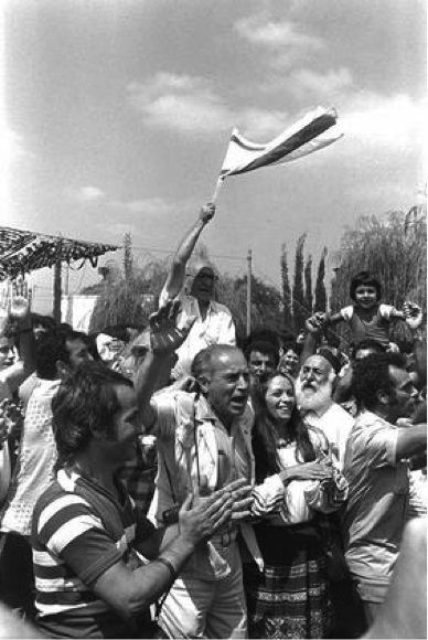 Israelis rejoice while awaiting the arrival of the rescued Entebbe hostages at Ben Gurion Airport on July 4, 1976.