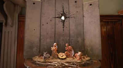 "Courtesy of JTA ""Scar of Bethlehem,"" an artwork depicting the nativity scene under a bullet hole instead of a star, by the street artist Banksy is on display at his Walled Off hotel in Bethlehem, Dec. 22, 2019."