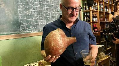 Courtesy of  Eliana Rudee via JNS Professor Aren Maeir, from Bar-Ilan University's Land of Israel studies and archaeology, models an ancient vessel and the new, recreated beer.