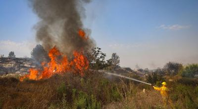 Courtesy of JTA Photo credit: Yossi Aloni  A firefighter works to extinguish a fire near the Kfar HaOranim settlement in the West Bank on Oct. 9, 2020, after all the residents were evacuated from the community.
