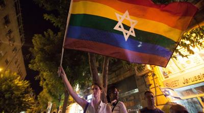 Courtesy of Omer Messinger/NurPhoto via Getty Images via JTA  A woman waves a Jewish Pride flag in Jerusalem on Aug. 1, 2015.