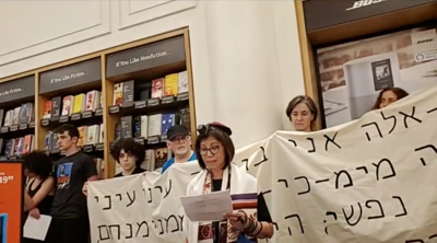 Courtesy of Screenshot from Facebook video  via JTA  A demonstrator speaks at a Jewish protest against Amazon at one of the company's brick-and-mortar stores in New York City, Aug. 11, 2019. The protest was held on Tisha B'Av, a traditional Jewish day of mourning. Behind the speaker is a banner with a Hebrew quotation from the Book of Lamentations.