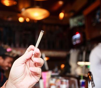 Man smoking marijuana cigarette in coffee shop in Amsterdam, Netherlands