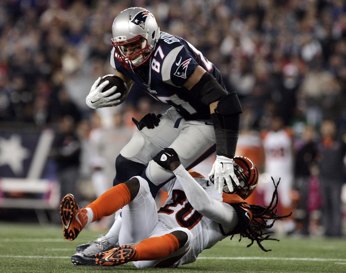 New England Patriots tight end Rob Gronkowski (87) runs over Cincinnati Bengals safety Reggie Nelson (20) after catching a short pass from quarterback Tom Brady.