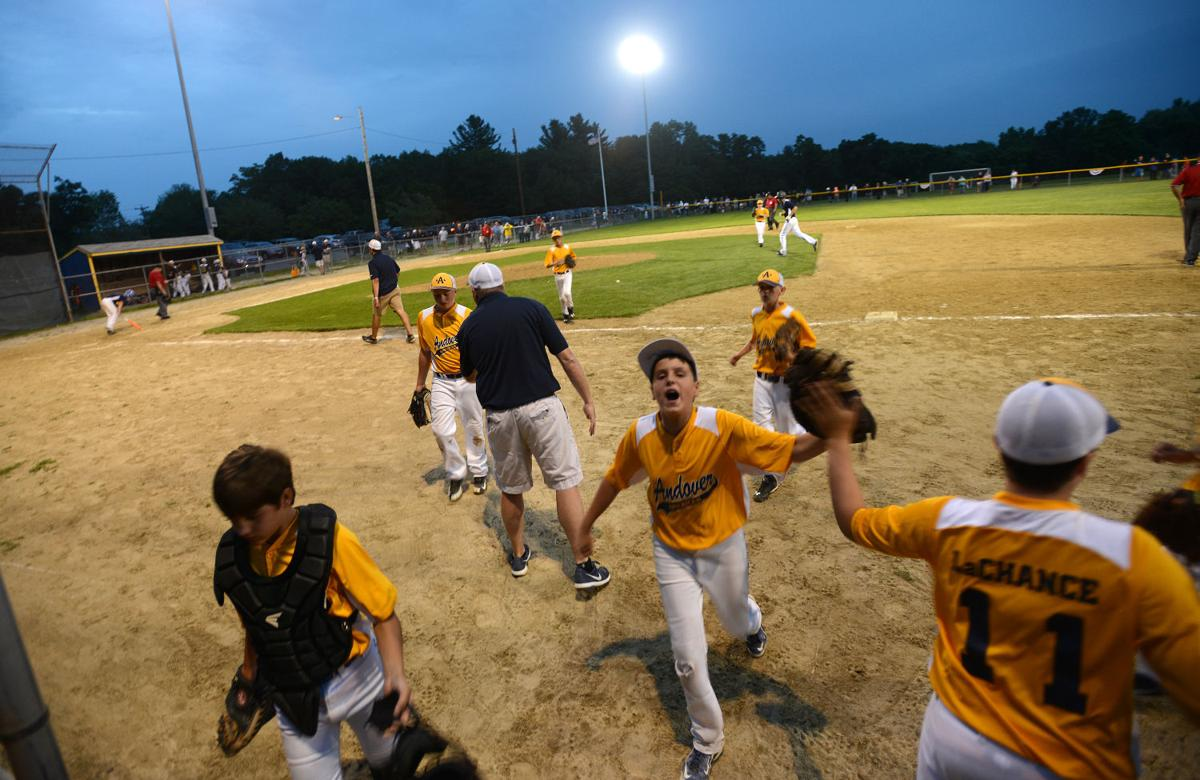 Andover American's Anthony Teberio, center, cheers his team on as they leave the field after closing out the third inning of Thursday's semifinal game against Andover National. National won 8-2.