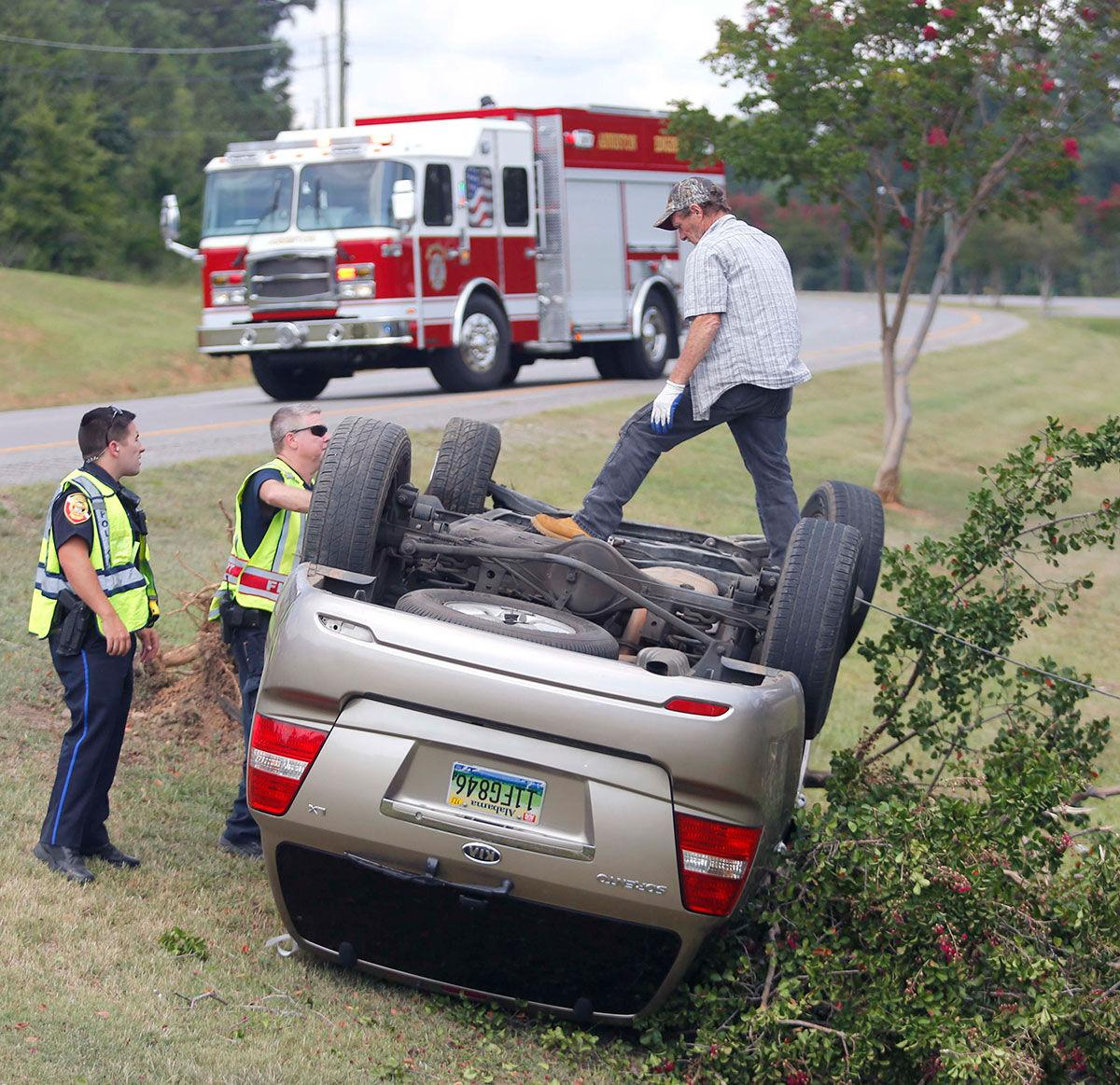 First responders and a tow truck driver from anniston auto body shop study how to turn the vehicle back over a car accident along mcclellan boulevard