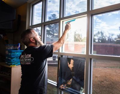 Jerry Wilks tints windows at Eden Elementary library