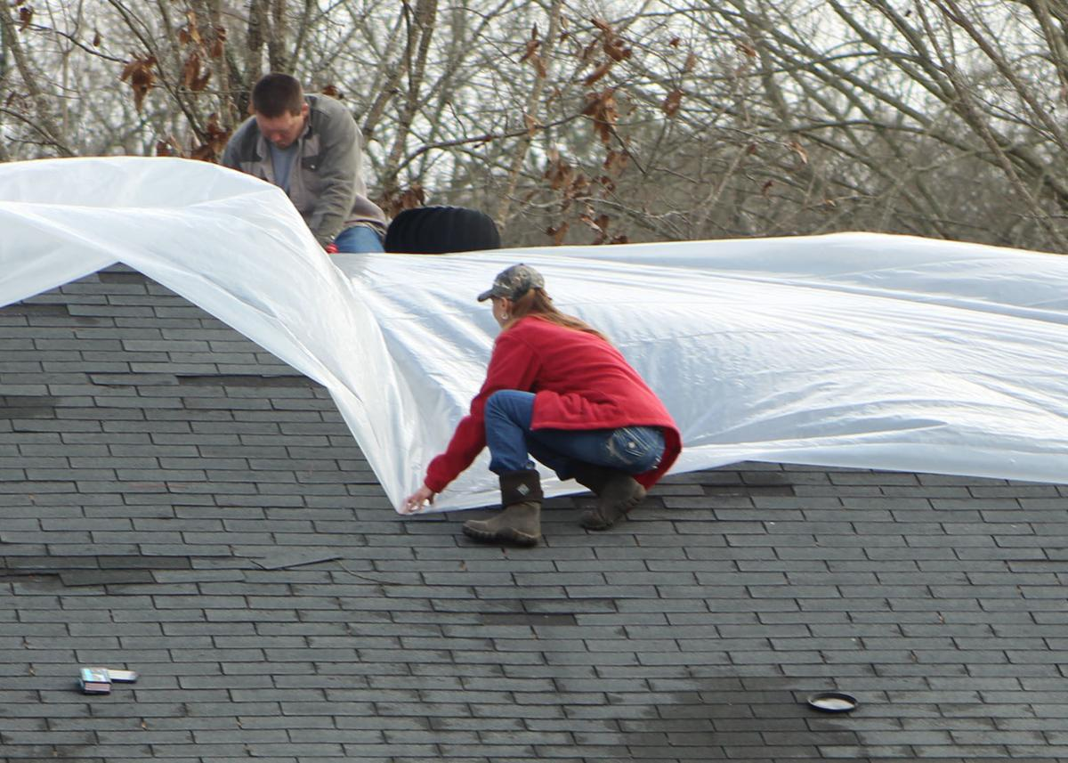 Binns Loop resident works to cover damaged roof