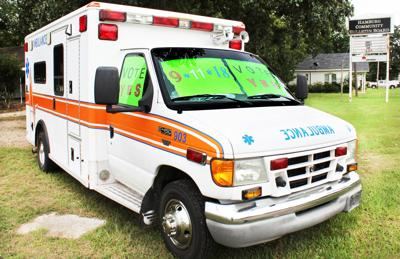 Ambulance with signs implores voters to ratify tax