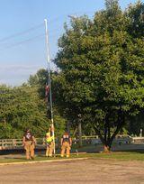 Nelsonville firefighters lower the flag