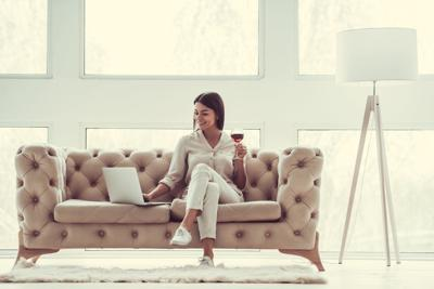 Women on couch with a drink and computer