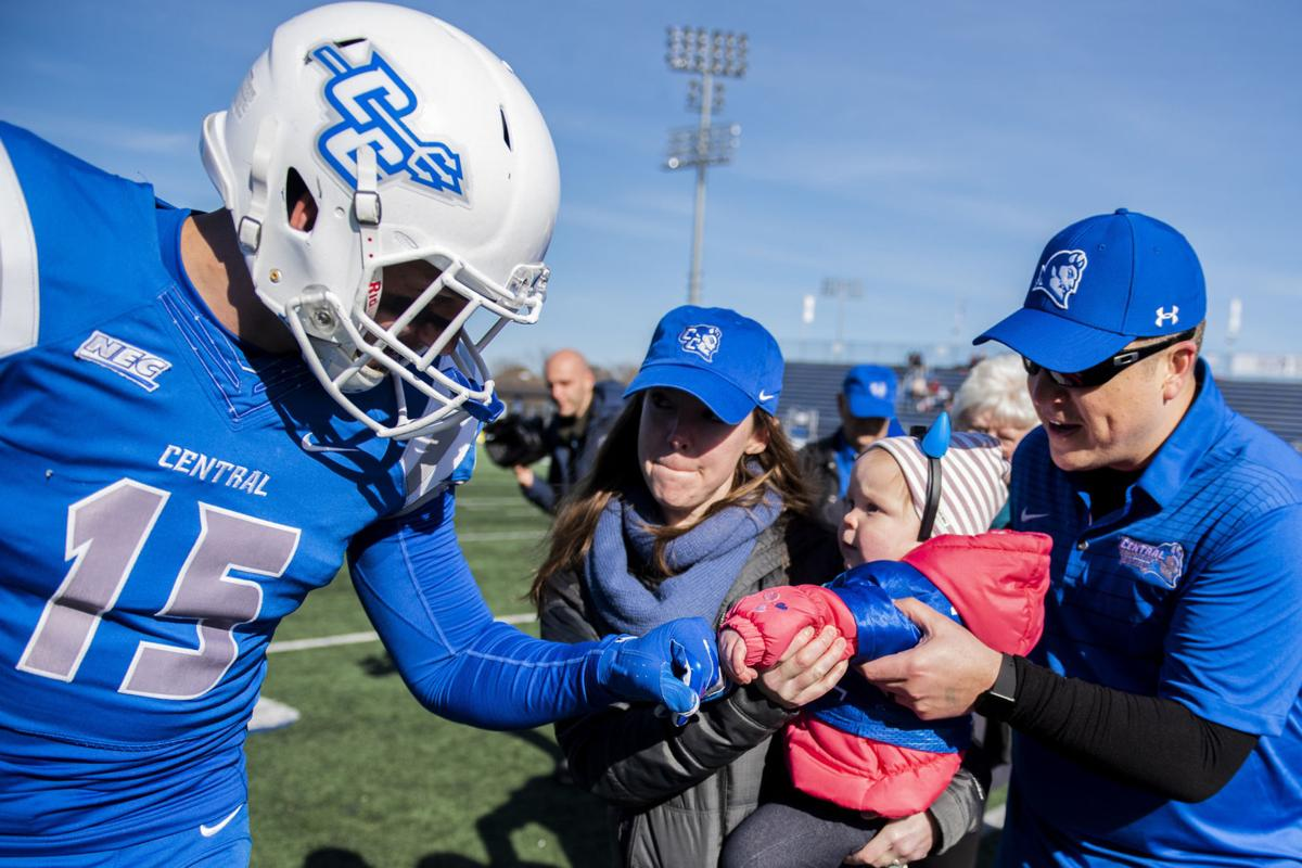 CCSU linebacker Mike Mushaw fist bumps Eleanor, almost 2, as she's held by her mom, Jess, and helped by her dad, Elan, after she tossed the coin before Saturday's 38-31 overtime victory over St. Francis in New Britain on Saturday, Nov. 9, 2019.