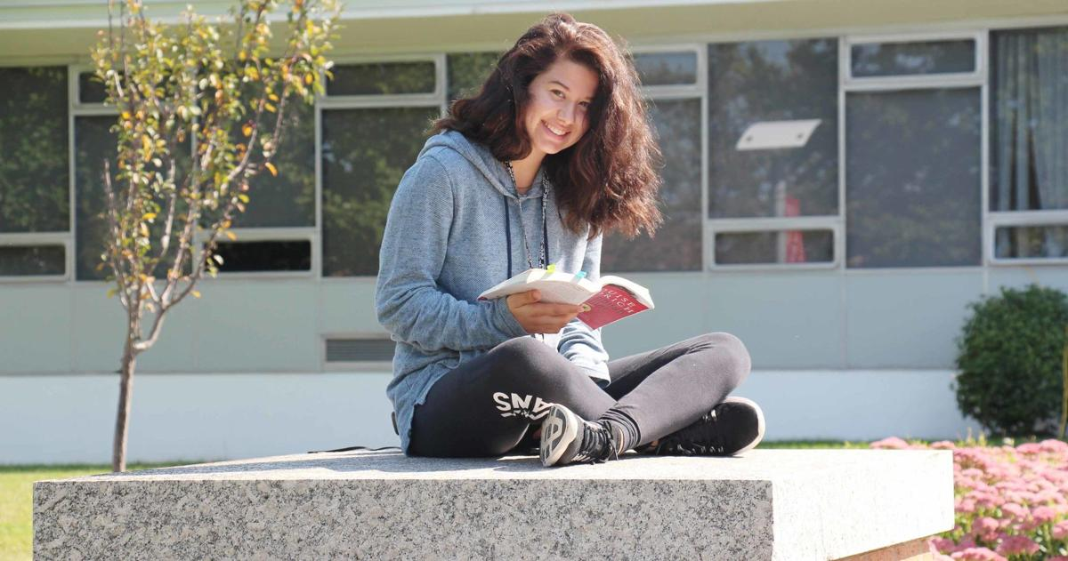 Student sitting outside on a bench with book